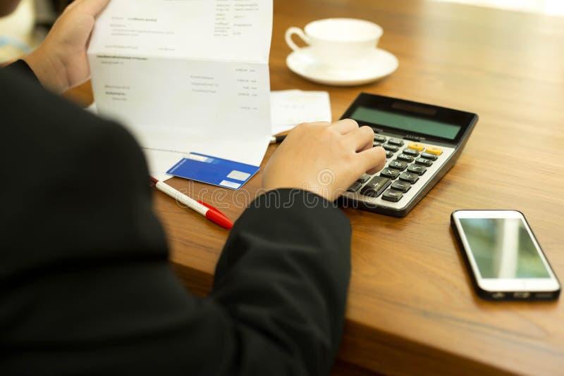 Επιχειρησιακή γυναίκα που κάνει τους οικονομικούς λογαριασμούς υπολογισμού από το πιστωτικό αυτοκίνητο στοκ εικόνες