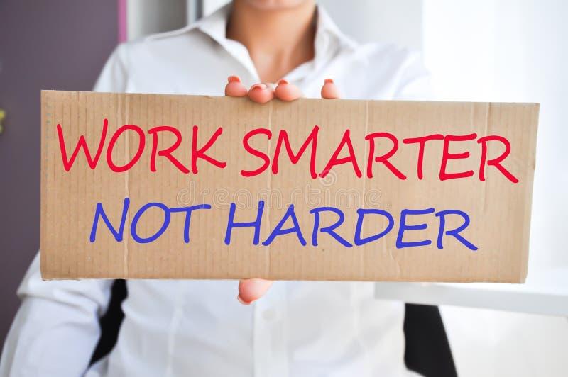 """Επιχειρησιακή γυναίκα που κρατά ένα έμβλημα με το """"Work εξυπνώτερο όχι harder† στοκ εικόνα με δικαίωμα ελεύθερης χρήσης"""