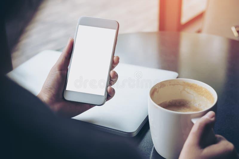 Επιχειρησιακή γυναίκα που κρατά το κινητό τηλέφωνο με την κενή άσπρη οθόνη με το φλυτζάνι latop και καφέ στον ξύλινο πίνακα στον  στοκ φωτογραφίες με δικαίωμα ελεύθερης χρήσης