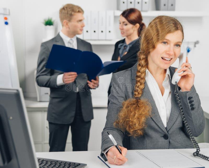 Επιχειρησιακή γυναίκα που μιλά στο τηλέφωνο στην αρχή στοκ εικόνες με δικαίωμα ελεύθερης χρήσης