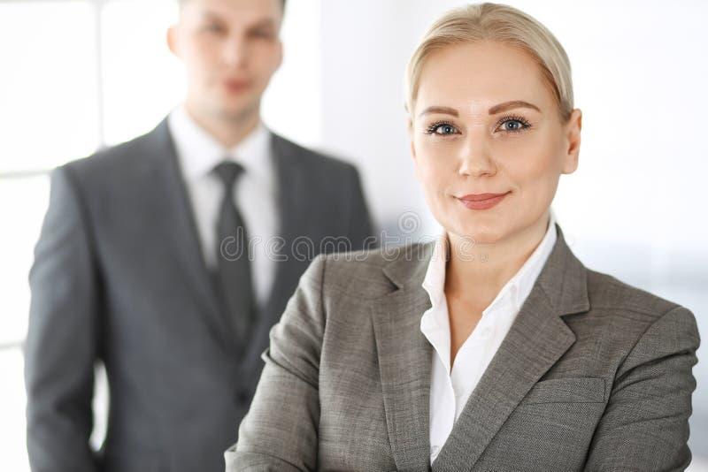 Επιχειρησιακή γυναίκα που στέκεται κατ' ευθείαν με τον επιχειρηματία συναδέλφων στην αρχή, headshot Επιτυχία και εταιρική συνεργα στοκ εικόνα