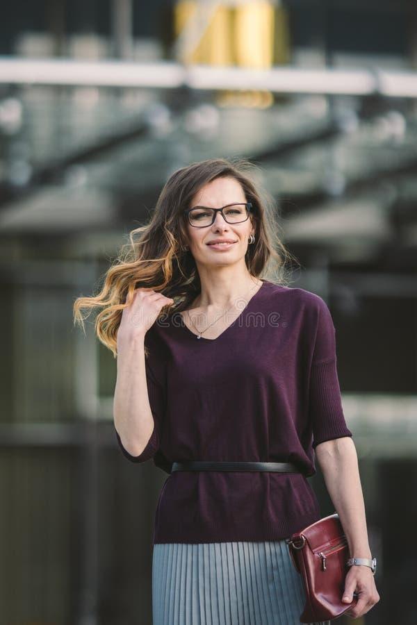 Επιχειρησιακή γυναίκα που στέκεται στην οδό ενάντια στο κτίριο γραφείων Εργασία επιχειρησιακών γυναικών πόλεων Χαμόγελο επιχειρησ στοκ εικόνες