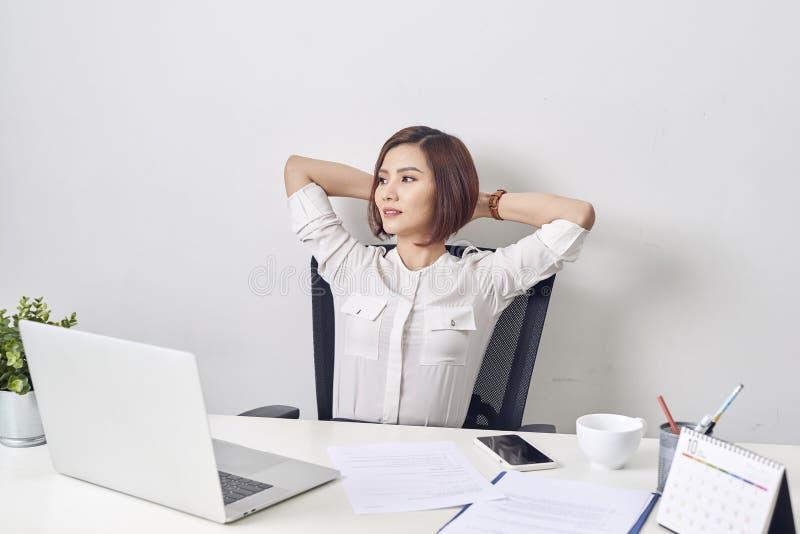 Επιχειρησιακή γυναίκα που στηρίζεται στο γραφείο μετά από μια κλίση εργάσιμης ημέρας στοκ εικόνες με δικαίωμα ελεύθερης χρήσης