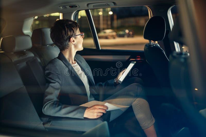 Επιχειρησιακή γυναίκα που ταξιδεύει με το αυτοκίνητο τή νύχτα στο επαγγελματικό ταξίδι στοκ φωτογραφία με δικαίωμα ελεύθερης χρήσης