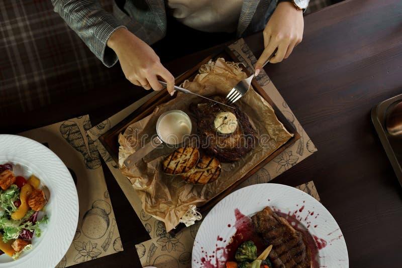 Επιχειρησιακή γυναίκα που τρώει την μπριζόλα βόειου κρέατος με το βούτυρο στον ξύλινο πίνακα σε ένα εστιατόριο Χρόνος για το υγιέ στοκ φωτογραφία