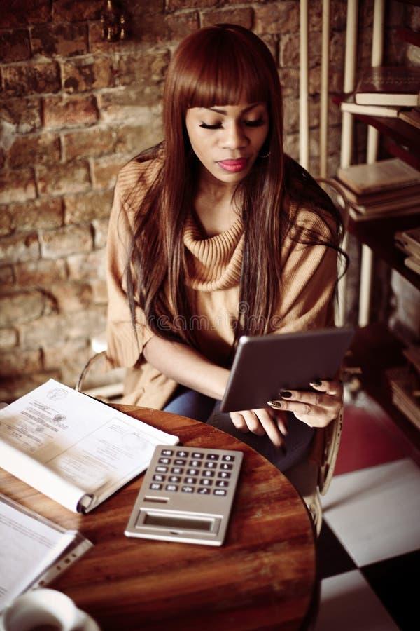 Επιχειρησιακή γυναίκα που υπολογίζει στην εργασία στοκ εικόνες
