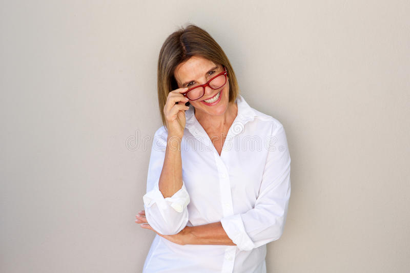 Επιχειρησιακή γυναίκα που χαμογελά και που κρατά τα γυαλιά στοκ εικόνες