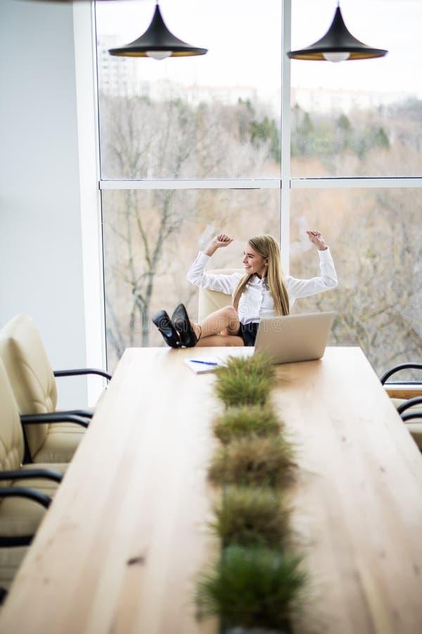 Επιχειρησιακή γυναίκα που χαλαρώνουν και διάθεση της καλοψημένης εργασίας στοκ εικόνα