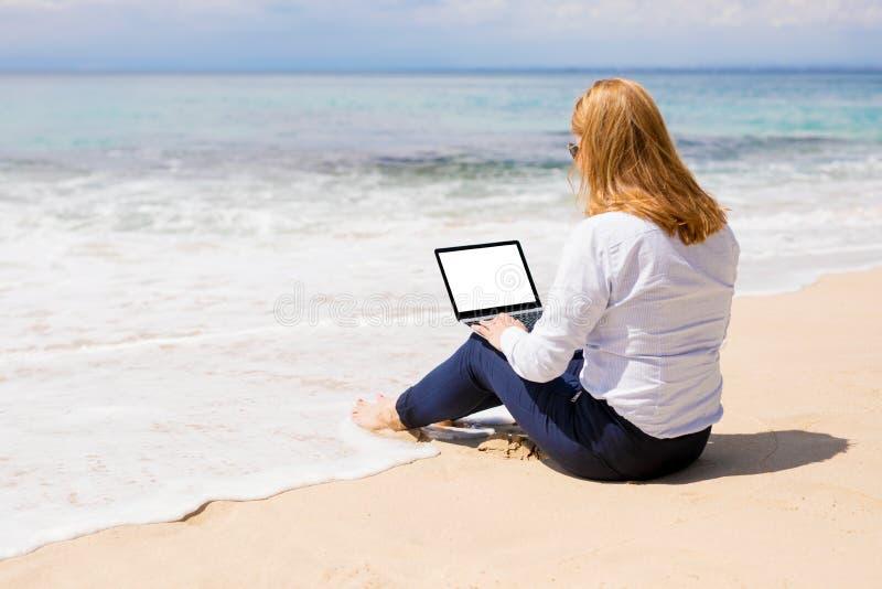 Επιχειρησιακή γυναίκα που χρησιμοποιεί το lap-top με την κενή άσπρη οθόνη στην παραλία στοκ εικόνα