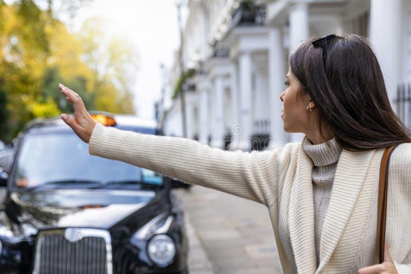 Επιχειρησιακή γυναίκα στο Λονδίνο που χαιρετά για ένα μαύρο ταξί στοκ εικόνα με δικαίωμα ελεύθερης χρήσης