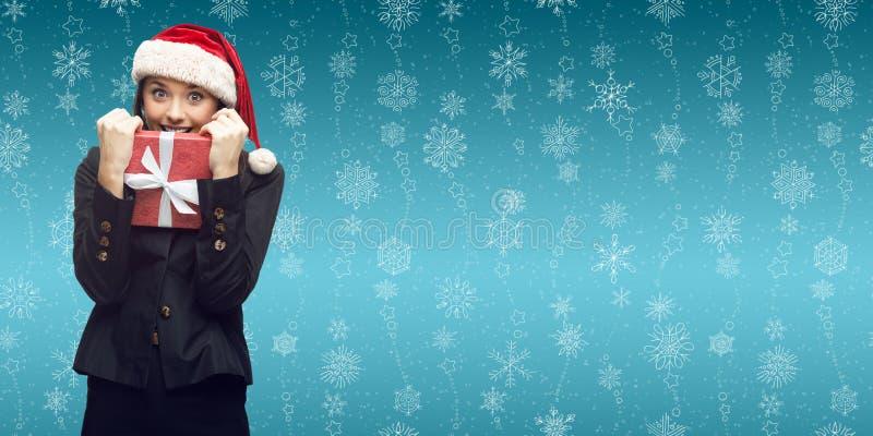 Επιχειρησιακή γυναίκα στο δώρο εκμετάλλευσης καπέλων santa στοκ εικόνες