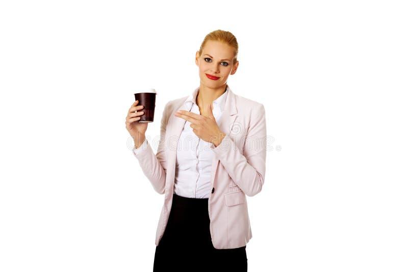 Επιχειρησιακή γυναίκα χαμόγελου που δείχνει για το φλυτζάνι εγγράφου στοκ εικόνα με δικαίωμα ελεύθερης χρήσης