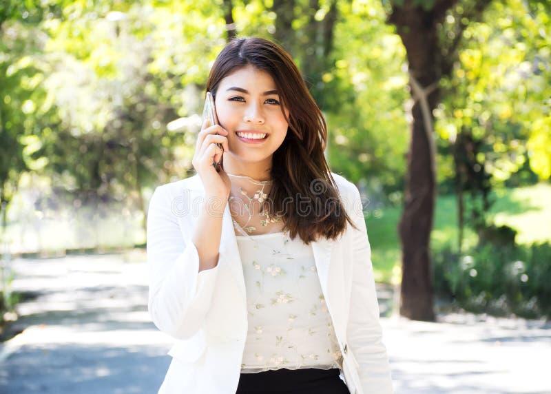 Επιχειρησιακή γυναίκα Beautyful που περπατά και που χρησιμοποιεί το έξυπνο τηλέφωνο στο πάρκο στοκ φωτογραφίες