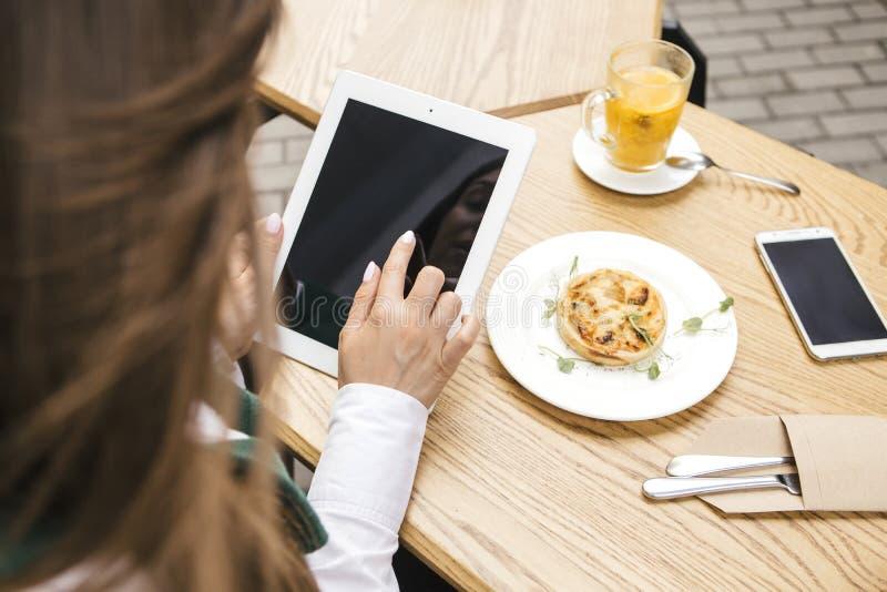 Επιχειρησιακή γυναίκα Brunette που εργάζεται ως freelancer από έναν καφέ στο θερινό πεζούλι Πίνει τις συσκευές τσαγιού και χρήσης στοκ φωτογραφία με δικαίωμα ελεύθερης χρήσης