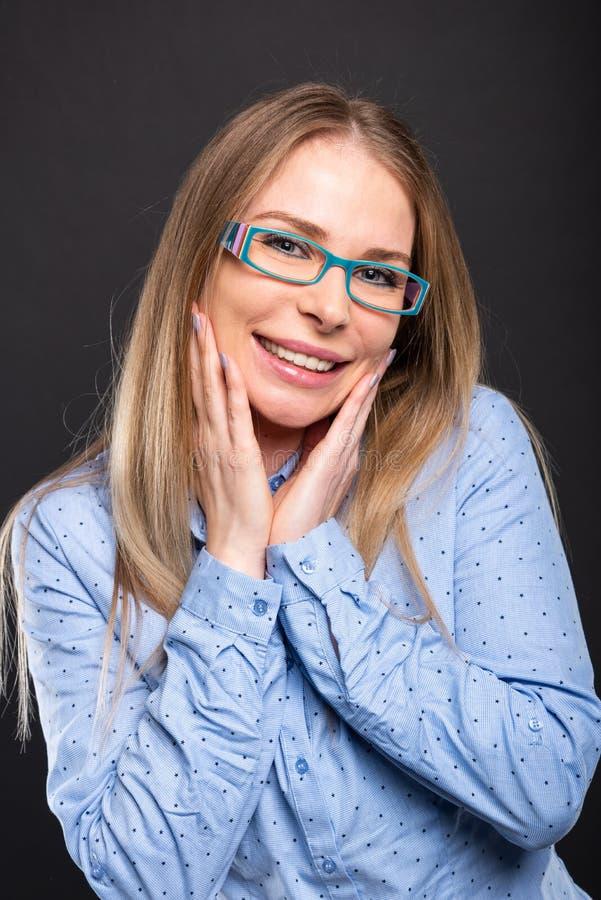 Επιχειρησιακή κυρία που φορά την μπλε τοποθέτηση γυαλιών που φαίνεται ευτυχή στοκ φωτογραφία με δικαίωμα ελεύθερης χρήσης