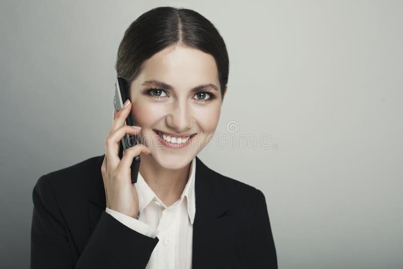 Επιχειρησιακή νέα γυναίκα στο τηλέφωνο που απομονώνεται πέρα από ένα γκρίζο backgrou στοκ φωτογραφίες με δικαίωμα ελεύθερης χρήσης