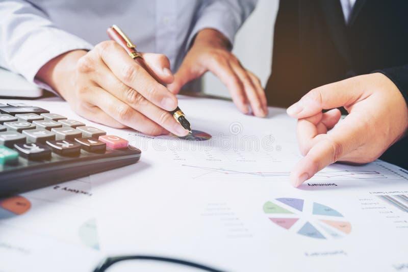Επιχειρησιακή ομάδα δύο συνάδελφοι που συζητούν τη νέα οικονομική γραφική παράσταση σχεδίων στοκ εικόνα