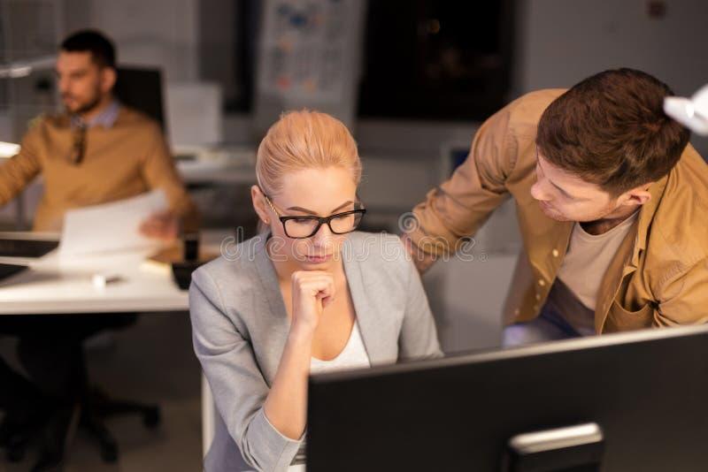 Επιχειρησιακή ομάδα με τον υπολογιστή που λειτουργεί αργά στο γραφείο στοκ εικόνα με δικαίωμα ελεύθερης χρήσης