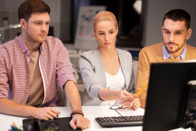 Επιχειρησιακή ομάδα με τον υπολογιστή που λειτουργεί αργά στο γραφείο στοκ εικόνα