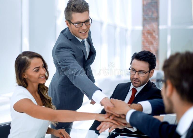 Επιχειρησιακή ομάδα που βάζει τα χέρια τους μαζί πέρα από το γραφείο στοκ εικόνα με δικαίωμα ελεύθερης χρήσης