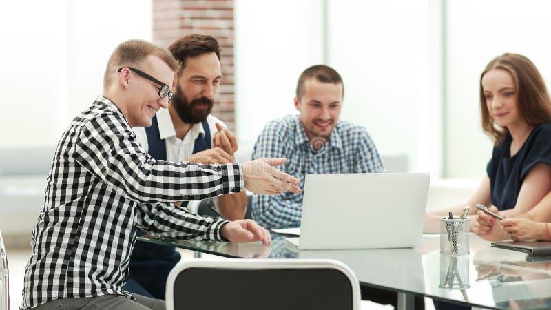 Επιχειρησιακή ομάδα που εξετάζει την οθόνη lap-top και που συζητά τις ιδέες τους στοκ εικόνες