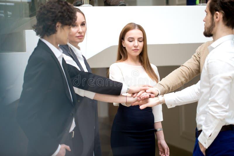 Επιχειρησιακή ομάδα που παρουσιάζει ενότητα με τα χέρια τους από κοινού στοκ εικόνα