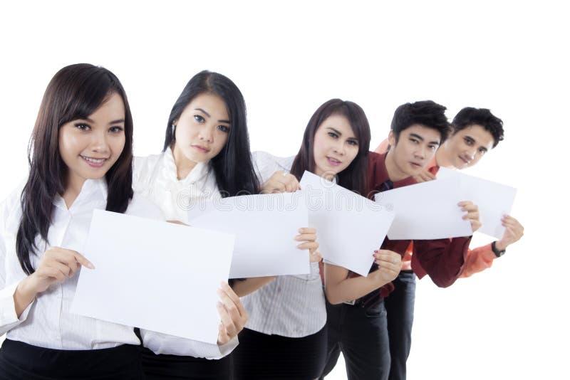 Επιχειρησιακή ομάδα που παρουσιάζει κενά έγγραφα για το στούντιο στοκ φωτογραφία με δικαίωμα ελεύθερης χρήσης