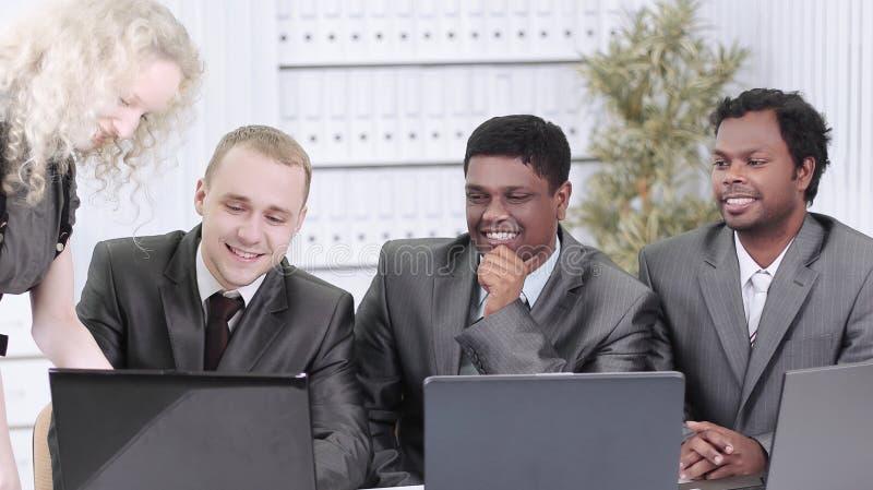 Επιχειρησιακή ομάδα που συζητά τα επιχειρησιακά ζητήματα που κάθονται στο γραφείο τους στοκ εικόνα