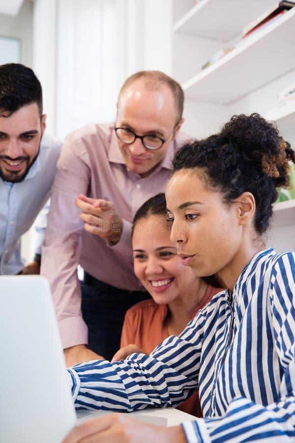 Επιχειρησιακή ομάδα τεσσάρων που εξετάζουν ένα lap-top στοκ εικόνες με δικαίωμα ελεύθερης χρήσης