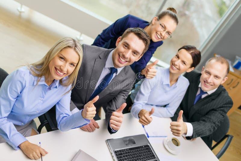 Επιχειρησιακή ομάδα που παρουσιάζει αντίχειρες επάνω στην αρχή στοκ εικόνα
