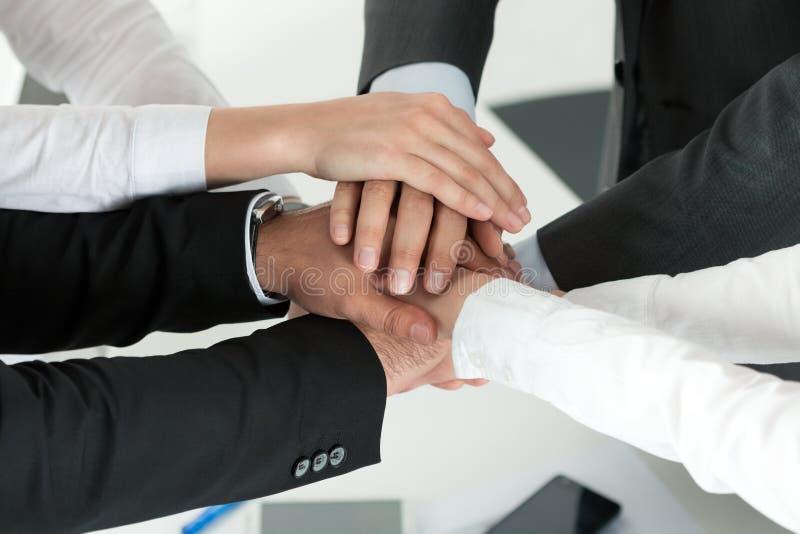 Επιχειρησιακή ομάδα που παρουσιάζει ενότητα με να βάλει τα χέρια τους από κοινού στοκ φωτογραφία με δικαίωμα ελεύθερης χρήσης