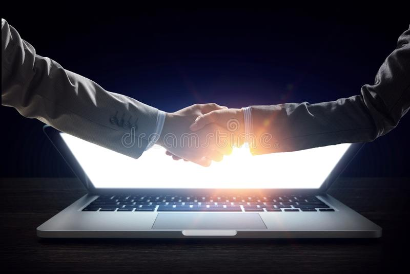 Επιχειρησιακή χειραψία από έναν άνδρα και μια γυναίκα, και ένα lap-top στοκ φωτογραφίες με δικαίωμα ελεύθερης χρήσης