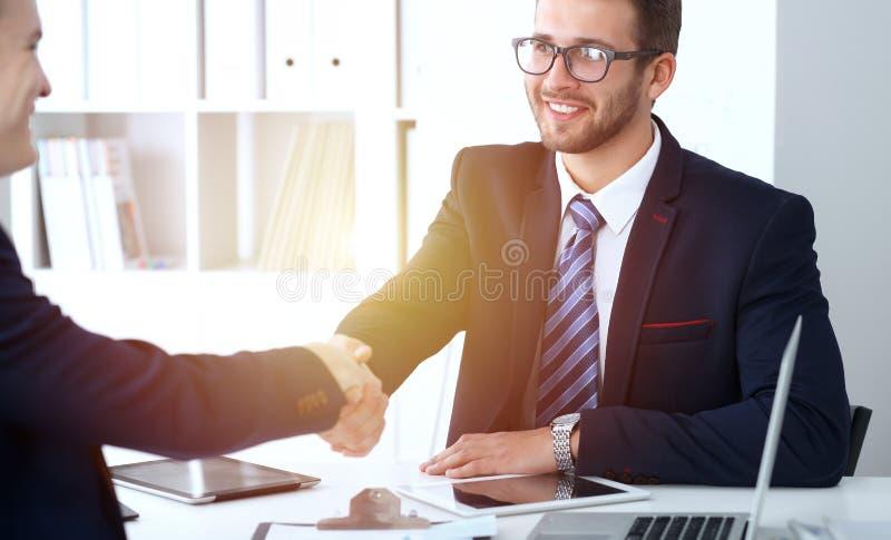 Επιχειρησιακή χειραψία στη συνεδρίαση ή τη διαπραγμάτευση στο γραφείο Δύο συνεργάτες επιχειρηματιών ικανοποιούν επειδή υπογράφοντ στοκ εικόνα με δικαίωμα ελεύθερης χρήσης
