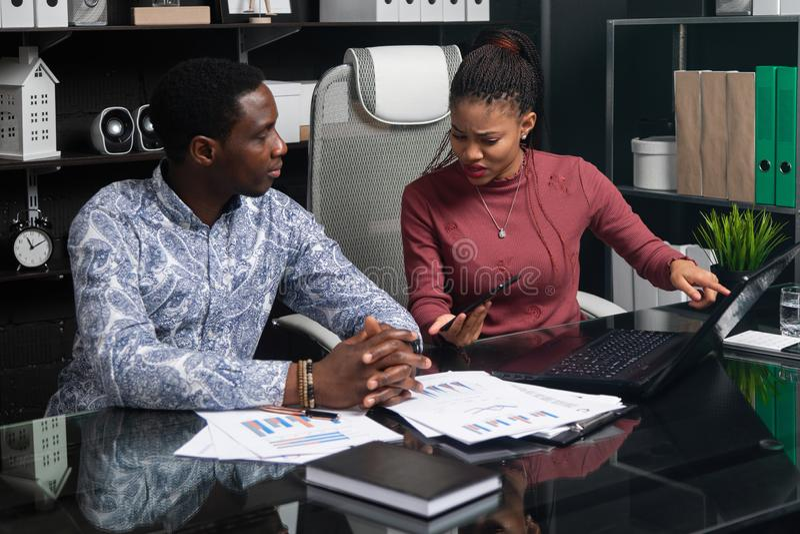 Επιχειρησιακοί νέοι της υπηκοότητας αφροαμερικάνων που εργάζονται με τα έγγραφα και το τηλέφωνο στον πίνακα στην αρχή στοκ εικόνα με δικαίωμα ελεύθερης χρήσης