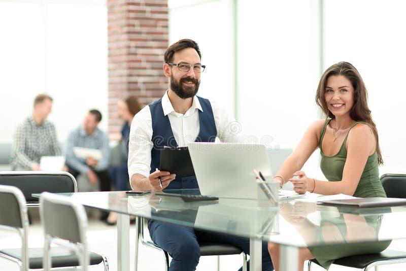 Επιχειρησιακοί συνάδελφοι που κάθονται στο γραφείο τους στο γραφείο στοκ φωτογραφίες
