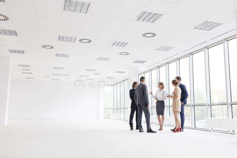 Επιχειρησιακοί συνάδελφοι που στέκονται συζητώντας στο νέο γραφείο στοκ φωτογραφίες