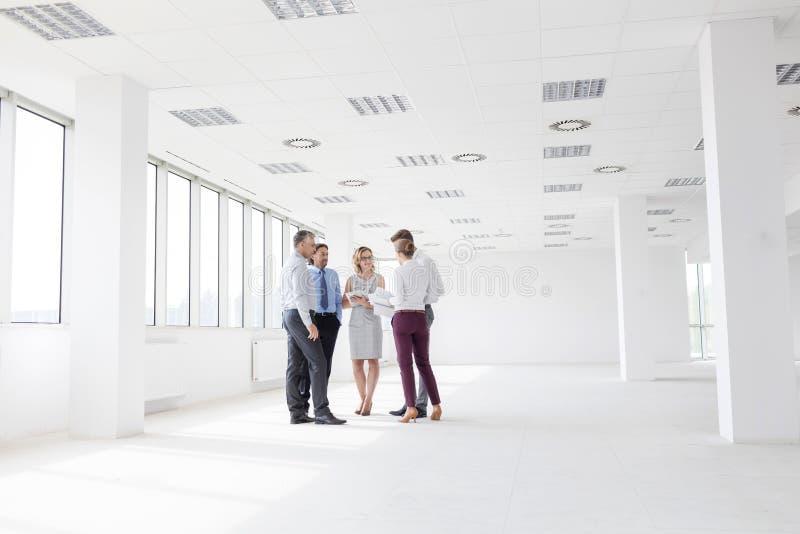 Επιχειρησιακοί συνάδελφοι που συζητούν στεμένος στο νέο γραφείο κατά τη διάρκεια της συνεδρίασης στοκ εικόνα με δικαίωμα ελεύθερης χρήσης