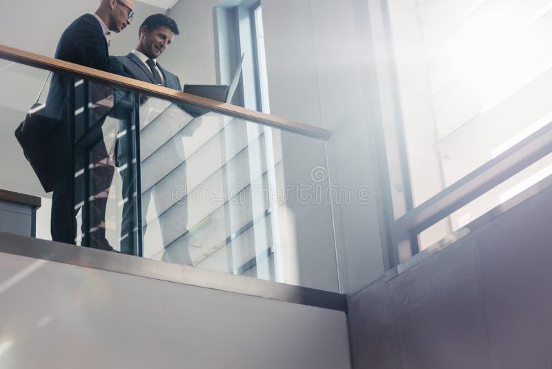 Επιχειρησιακοί συνάδελφοι που συζητούν την εργασία στην αρχή στοκ εικόνα