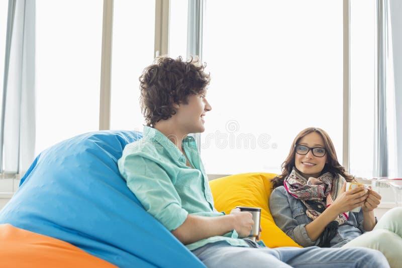 Επιχειρησιακοί συνάδελφοι που έχουν τον καφέ χαλαρώνοντας στις καρέκλες beanbag στο δημιουργικό γραφείο στοκ φωτογραφία με δικαίωμα ελεύθερης χρήσης