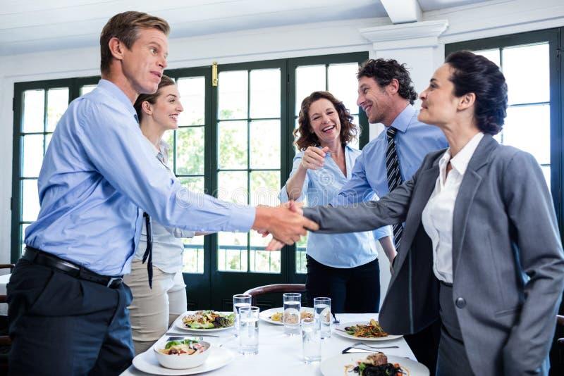 Επιχειρησιακοί συνάδελφοι που τινάζουν τα χέρια μετά από μια επιτυχή συνεδρίαση του μεσημεριανού γεύματος στοκ εικόνα