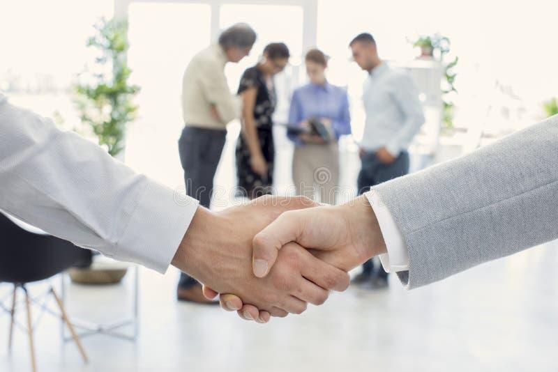 Επιχειρησιακοί χειραψία και επιχειρηματίες στοκ εικόνες