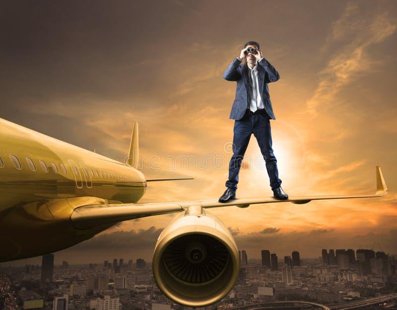 Επιχειρησιακό άτομο και φακός διοπτρών που στέκονται στην κατασκόπευση φτερών αεροπλάνων στοκ εικόνα με δικαίωμα ελεύθερης χρήσης