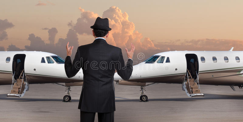 Επιχειρησιακό άτομο μπροστά από δύο ιδιωτικά αεριωθούμενα αεροπλάνα στοκ εικόνα
