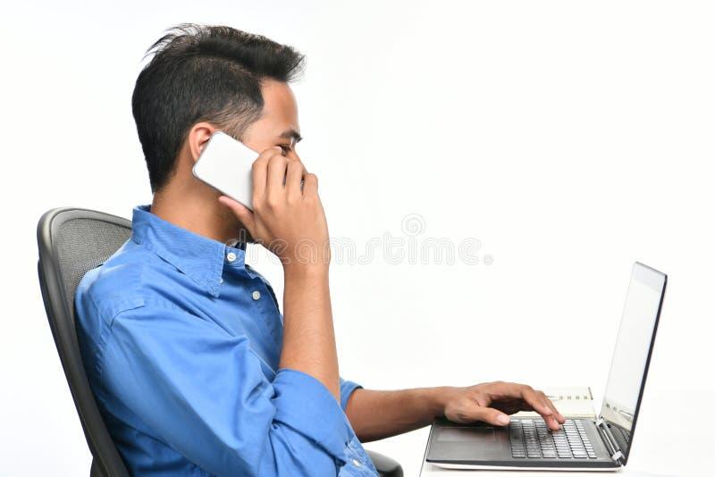 Επιχειρησιακό άτομο ξεκινήματος που χαμογελά μιλώντας στο τηλέφωνο και εργαζόμενος με το φορητό προσωπικό υπολογιστή στοκ εικόνες