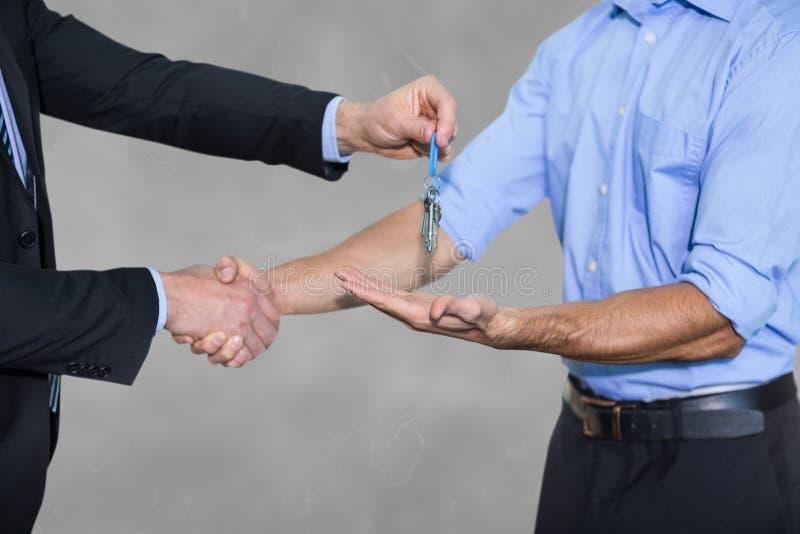 Επιχειρησιακό άτομο που δίνει τα κλειδιά και που τινάζει τα χέρια στοκ εικόνες