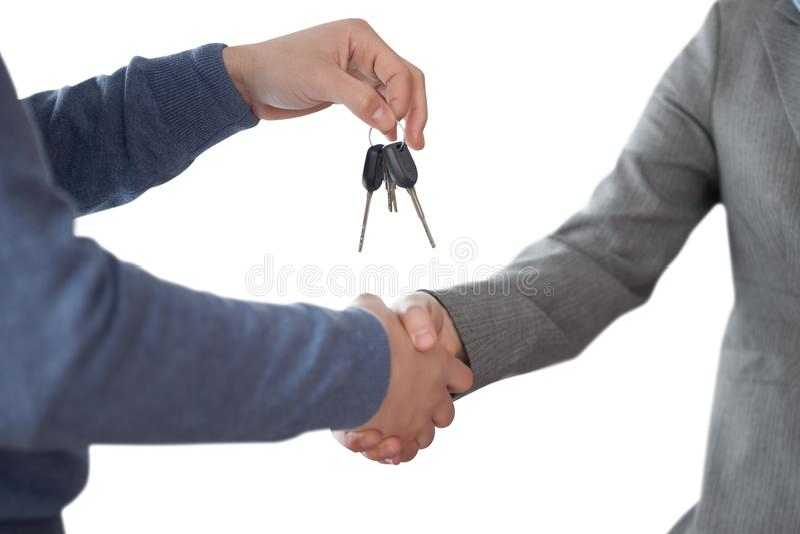 Επιχειρησιακό άτομο που δίνει τα κλειδιά και που τινάζει τα χέρια στοκ εικόνα με δικαίωμα ελεύθερης χρήσης