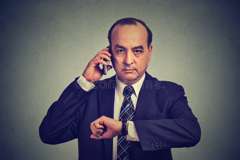 Επιχειρησιακό άτομο που εξετάζει το wristwatch, που μιλά στο κινητό τηλέφωνο που τρέχει αργά για τη συνεδρίαση Ο χρόνος είναι χρή στοκ φωτογραφία