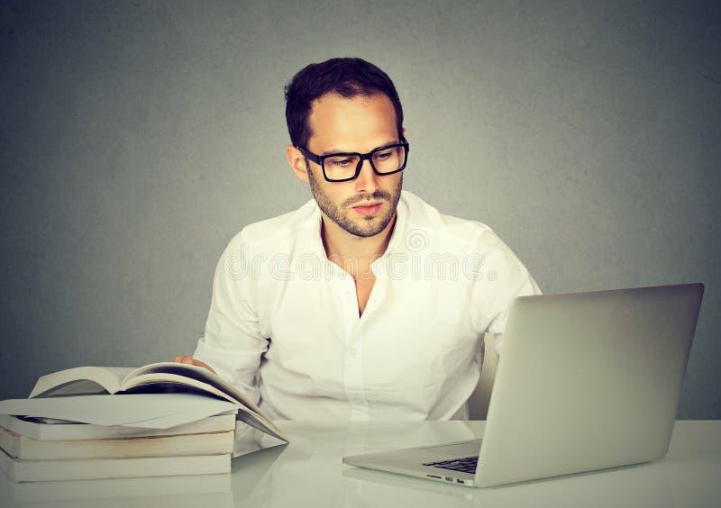 Επιχειρησιακό άτομο που εργάζεται με τα βιβλία ανάγνωσης lap-top στοκ εικόνες με δικαίωμα ελεύθερης χρήσης