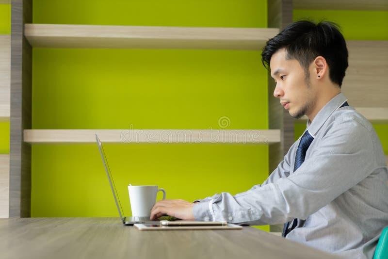 Επιχειρησιακό άτομο που εργάζεται με το φλυτζάνι καφέ κατανάλωσης lap-top νέα Ασία στοκ φωτογραφίες