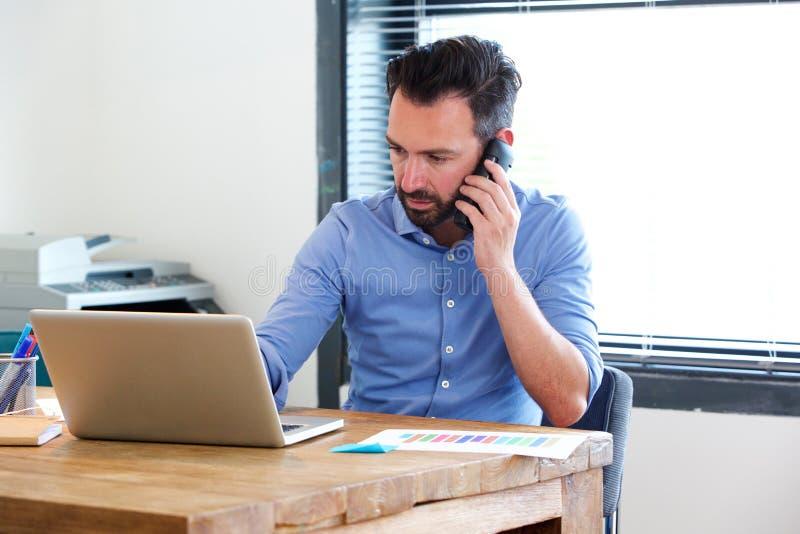 Επιχειρησιακό άτομο που εργάζεται στο lap-top και που μιλά στο κινητό τηλέφωνο στοκ φωτογραφίες